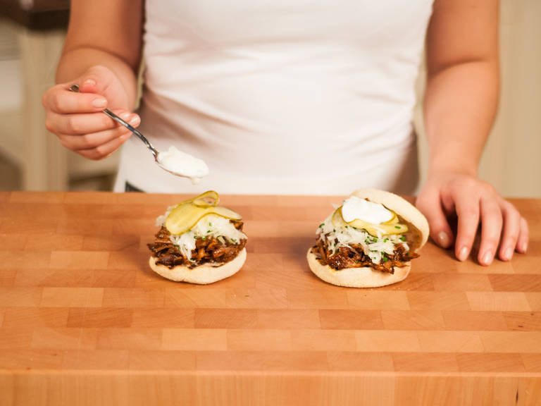 Preheat a grill pan over medium heat. Grill buns for approx. 1 - 2 min. on each side. Place shredded pork onto the bun. Serve topped with cabbage, pickles, and sour cream.