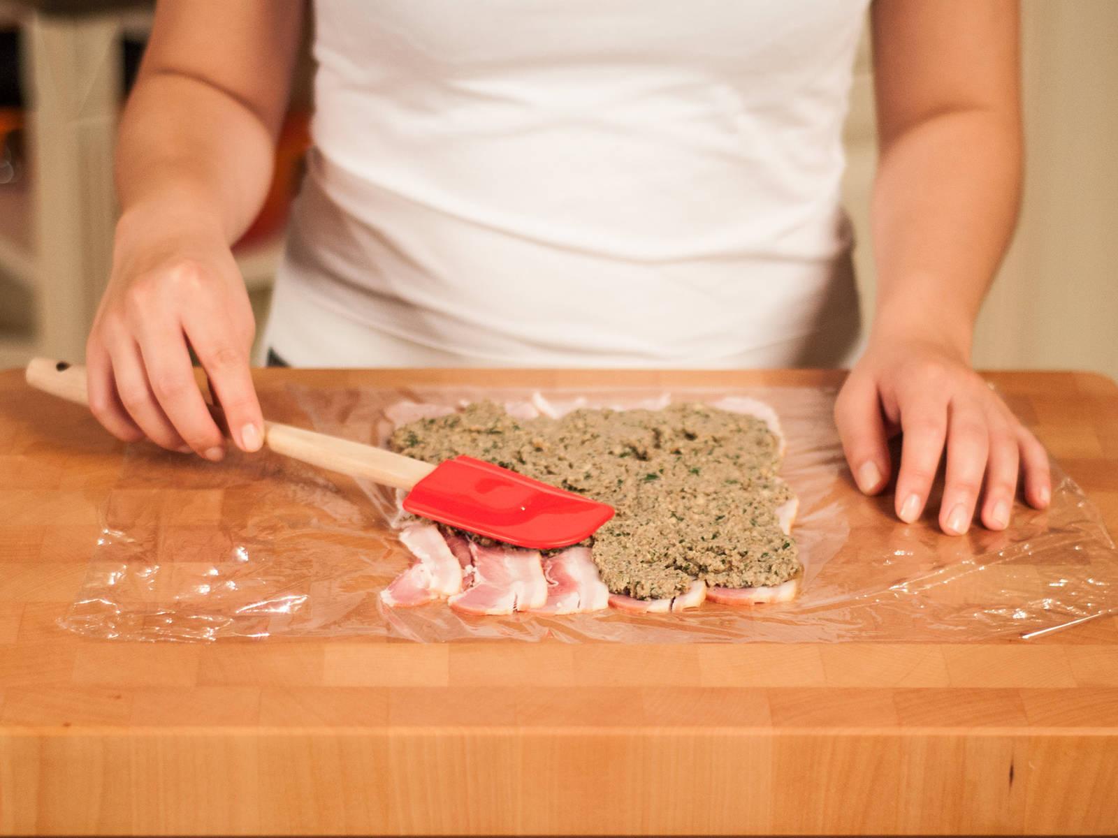 在砧板上铺一大张保鲜膜。将一半培根片排列在中间,将蘑菇泥铺在培根上,然后将牛里脊放在上面,将剩余的蘑菇泥铺在牛肉上,再盖上培根片。用保鲜膜包起来,使牛肉被蘑菇泥和培根紧紧包裹。放入冰箱冷藏30分钟左右。