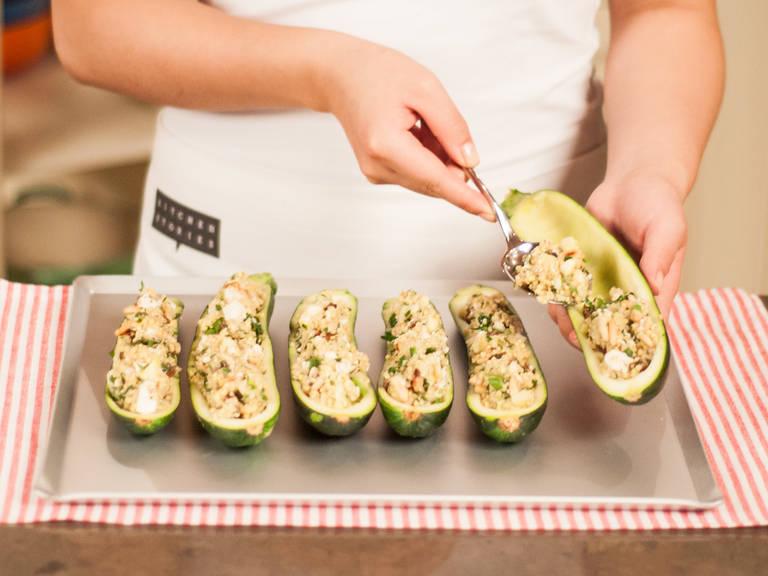 Falls nötig das Backblech mit Backpapier auslegen. Zucchini darauf platzieren und mit der vorbereiteten Masse füllen.