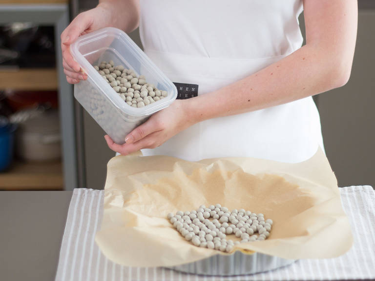 Flour working surface and roll out dough. Transfer to a greased tart pan. Carefully place a sheet of parchment paper on the dough and fill with pie weights or dried beans. Blind bake in preheated oven at 180°C/350°F for approx. 8 – 10 min. Set aside.