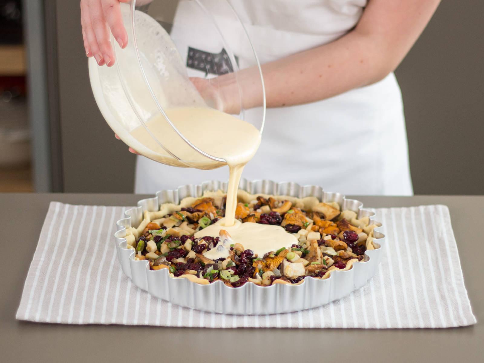 取出烤珠和烘焙纸,在面饼中填入蘑菇混合物。将酸奶油淋在蘑菇上方放入已预热的烤箱中,以 180°C/350°F 的温度烤制约 35 – 40 分钟。