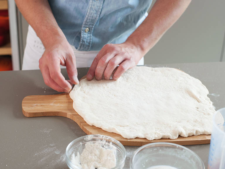 Remove dough from bowl. On a floured work surface, flatten out to approx. the size of the pizza stone. Transfer to a pizza paddle.