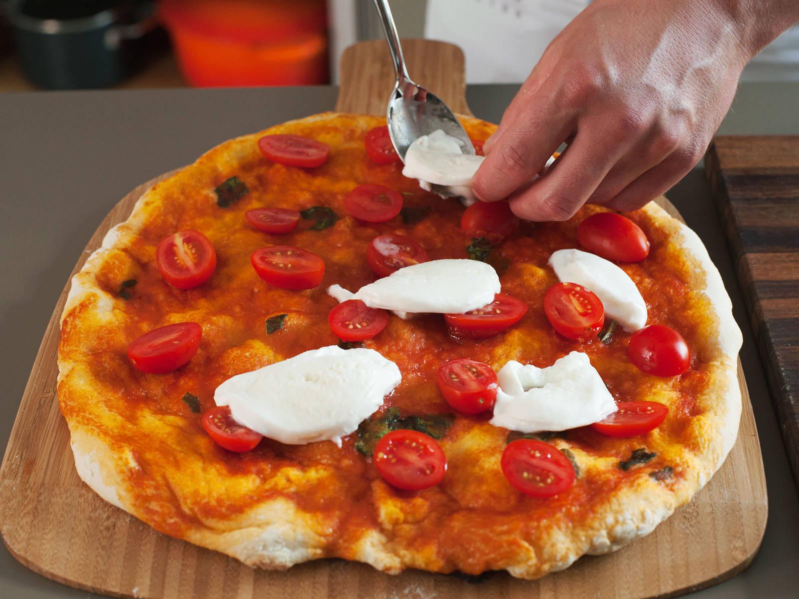 In der Zwischenzeit Kirschtomaten halbieren und Büffelmozzarella in dünne Scheiben schneiden. Pizza aus dem Ofen nehmen und mit Tomaten und Mozzarella belegen. Belegte Pizza zurück in den Ofen geben und für weitere 6 - 7 min. backen, bis der Käse geschmolzen und der Rand goldbraun ist.