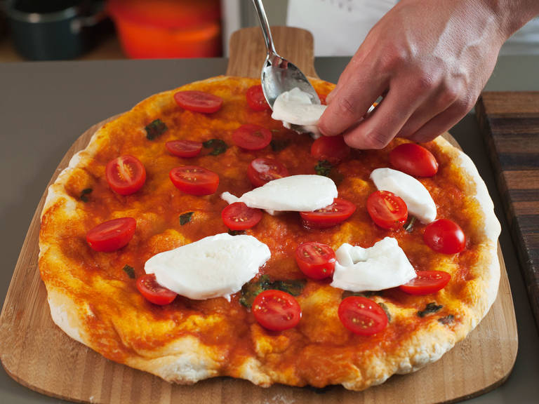 Meanwhile, cut cherry tomatoes in half and buffalo mozzarella into thin slices. Remove pizza from oven; place tomatoes and mozzarella on top, return to oven and bake for another 6 – 7 min. until cheese is melted and crust is golden.