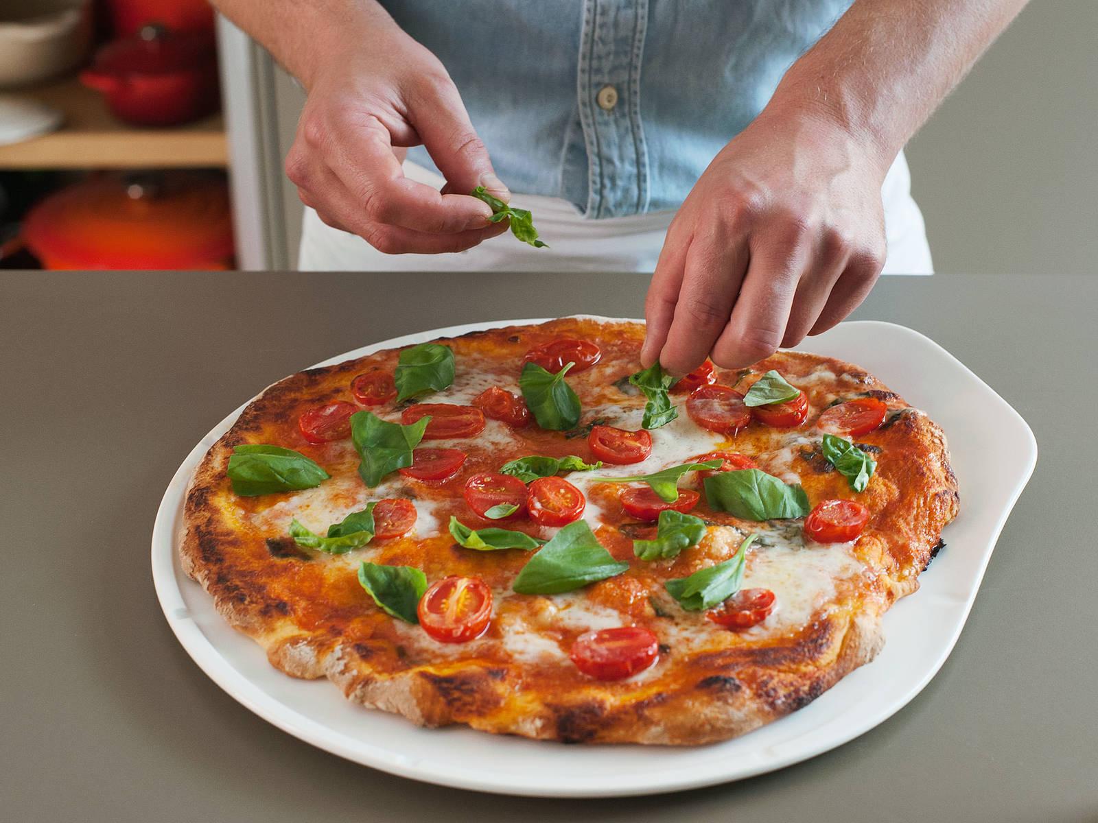 Pizza mit frischen Basilikumblättern verzieren. Auf Wunsch mit einem hochwertigen Olivenöl beträufelt servieren. Guten Appetit!