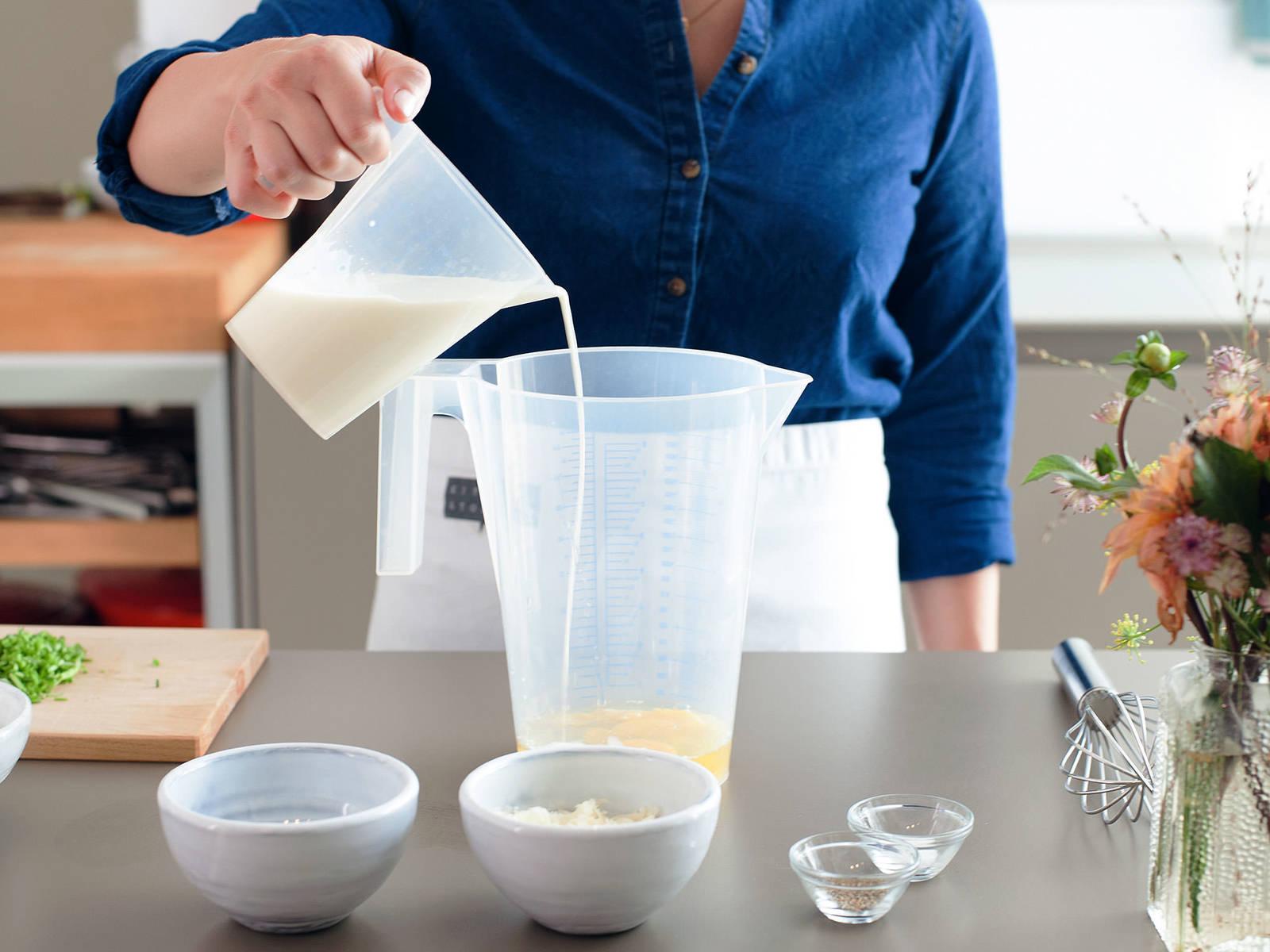 将烤箱预热至220℃。用黄油稍微润滑松饼烤盘。剁碎香葱,擦碎芝士。在大量杯中混合鸡蛋、牛奶和黄油,搅拌均匀。