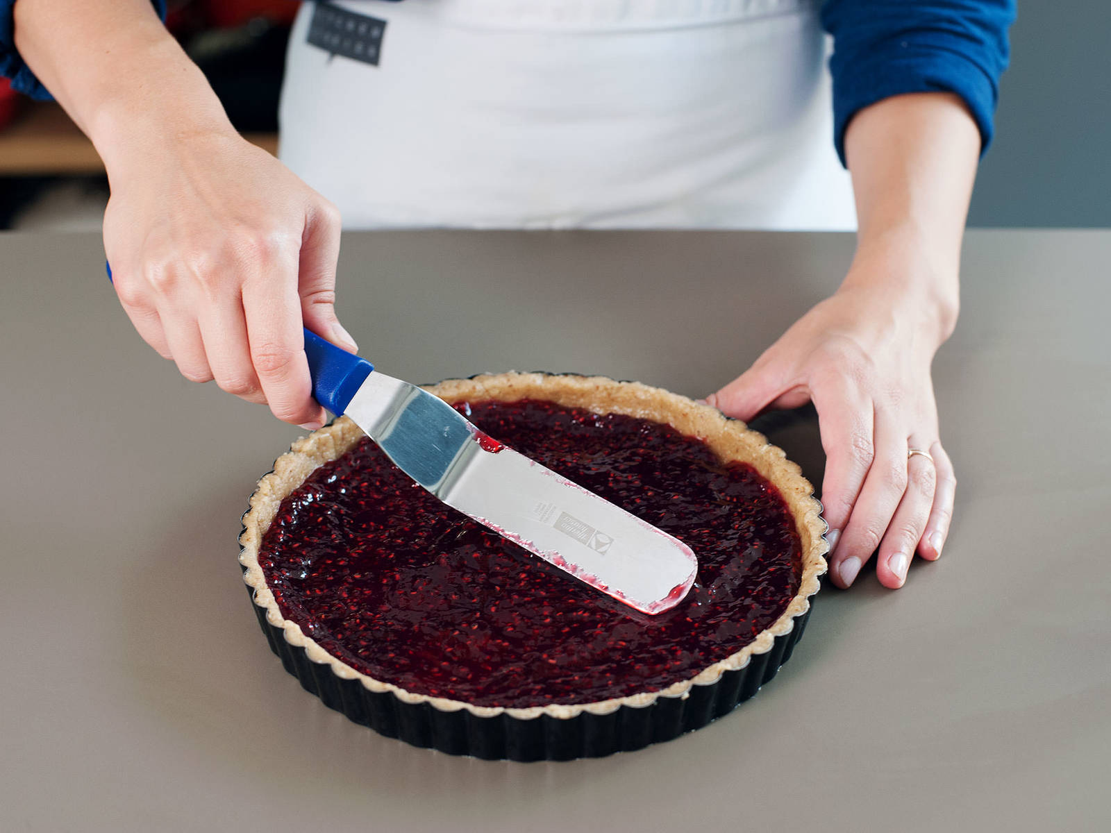 Marmelade gleichmäßig auf dem Teig verstreichen.
