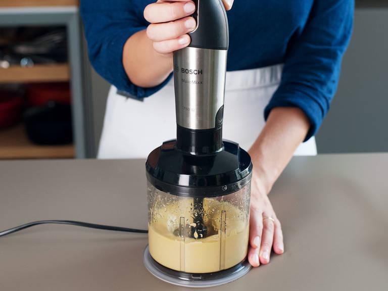 Währenddessen den Zitronensaft mit Senf, Knoblauch und Ahornsirup mit dem Schneebesen aufschlagen oder pürieren. Langsam das Olivenöl hinzufügen bis es emulgiert.