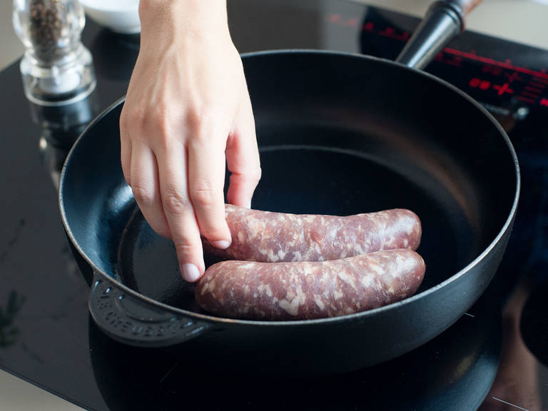 Place a large, heavy-bottomed sauté pan over medium heat; lightly oil pan, then add the sausages. Cook until browned and cooked through. Transfer to a paper towel-lined plate to drain and cool slightly, then slice.