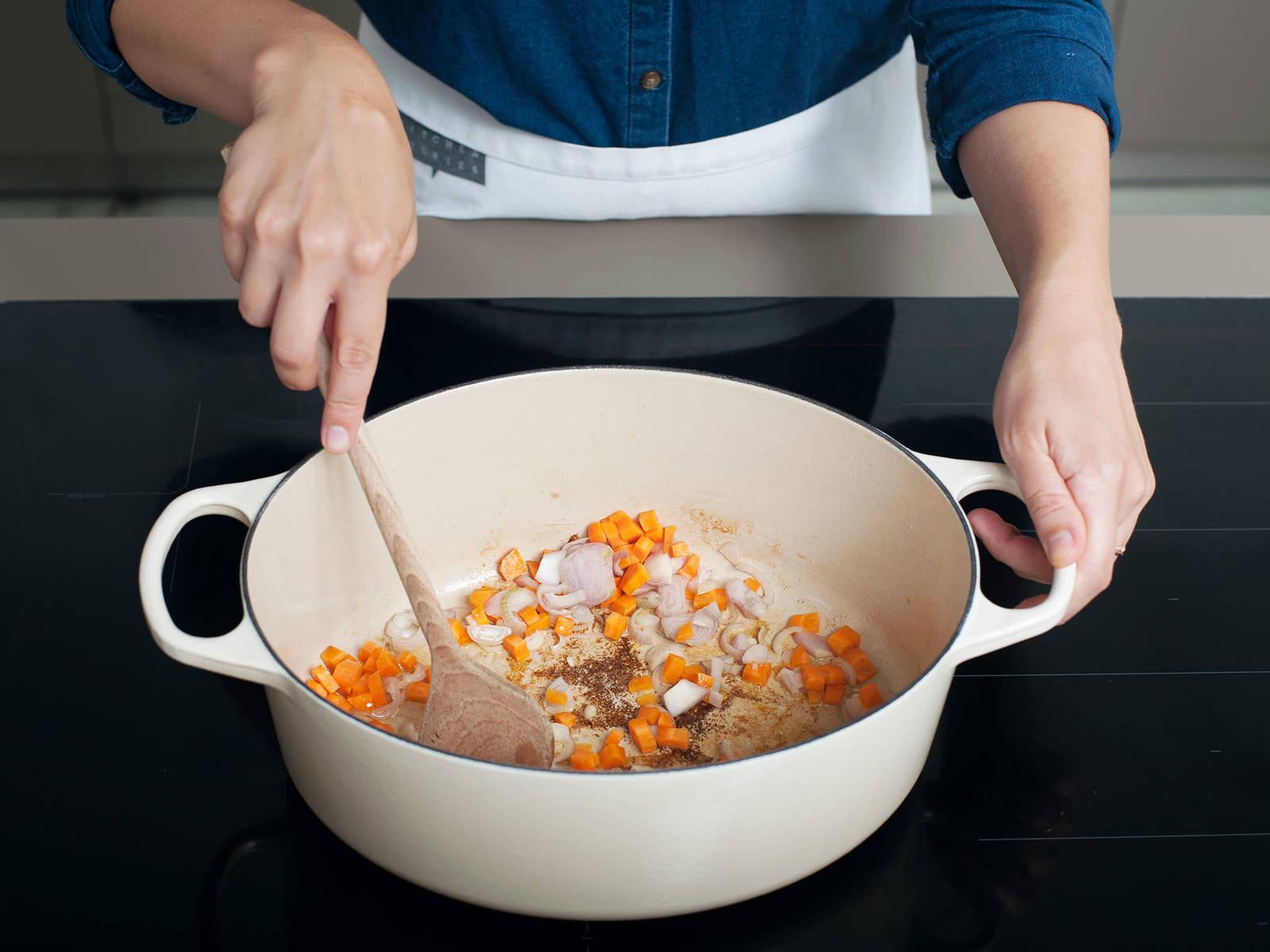 Ofen auf 150°C vorheizen. Vom ausgetretenen Fett fast alles entfernen und nur einen Rest zum Anbraten des Gemüse im Topf lassen. Anschließend Karotten, Knoblauch und Schalotten in den Topf geben. Bei mittlerer Hitze für 3 - 5 min. anschwitzen bis das Gemüse weich wird und anfängt zu duften.