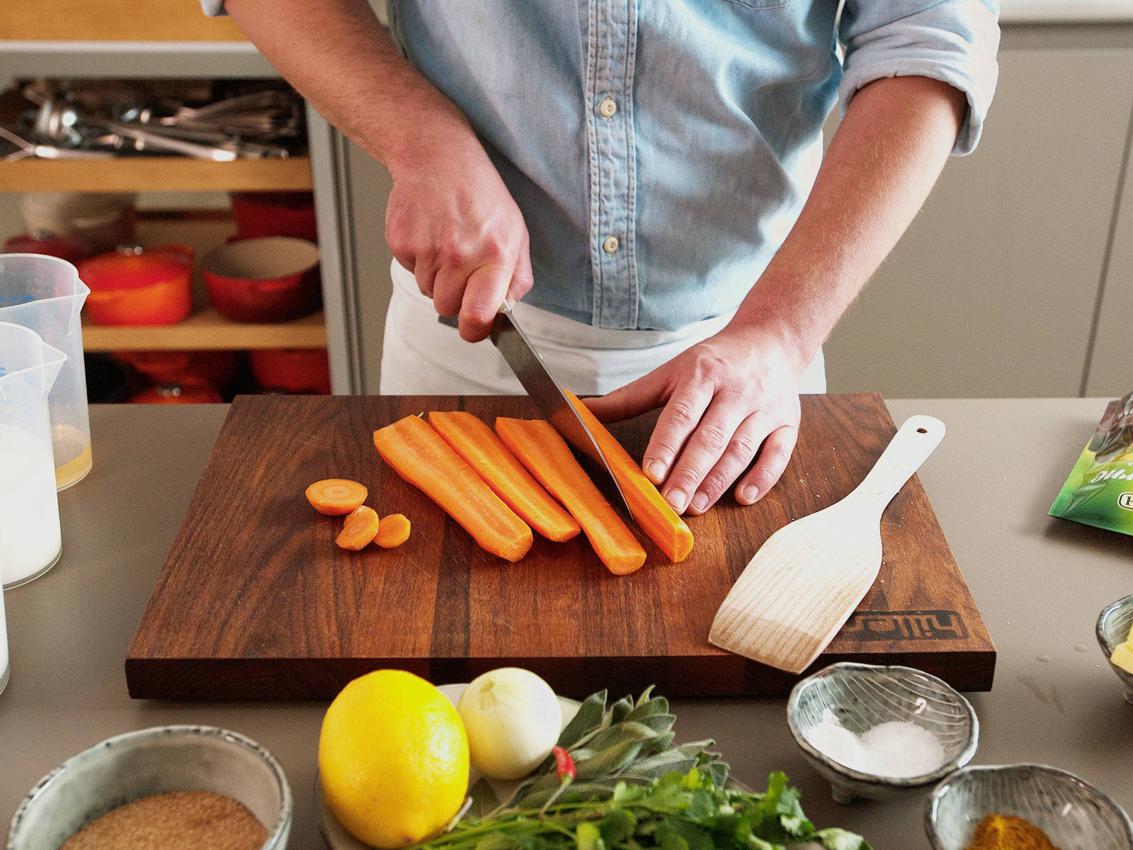 Backofen auf 180°C vorheizen. Zwiebeln schälen und grob schneiden, dann Karotten schälen und längs aufschneiden. Chili aufschneiden, Samen herauskratzen und hacken. Ca. die Hälfte des Salbeis hacken. Die Kürbishälfte und die Karotten in eine Auflaufform oder eine ofenfeste Pfanne geben.