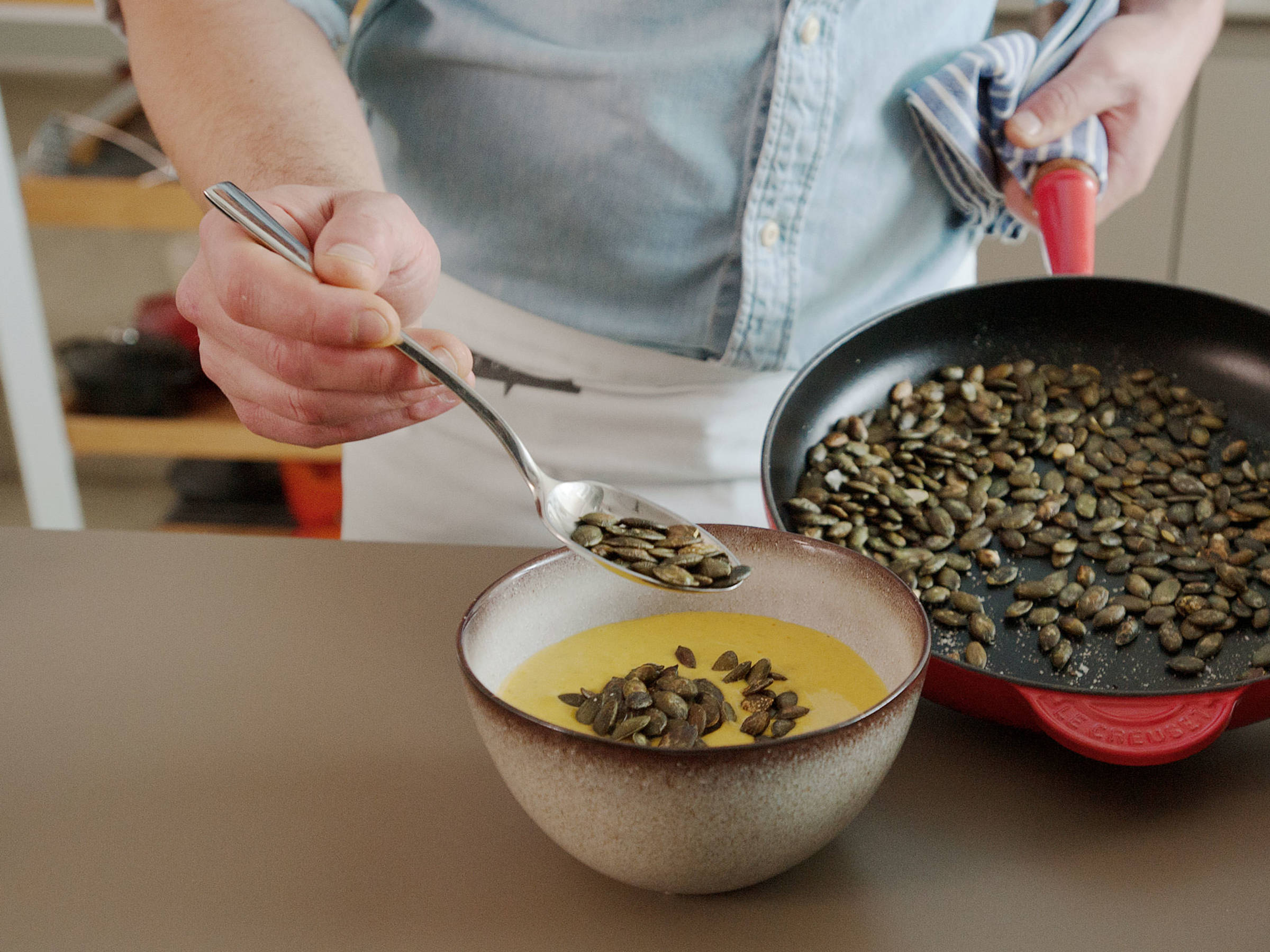 Turn off heat and stir in yogurt. With a hand blender, blend mixture until creamy. Serve with toasted pumpkin seeds and cilantro to taste. Enjoy!
