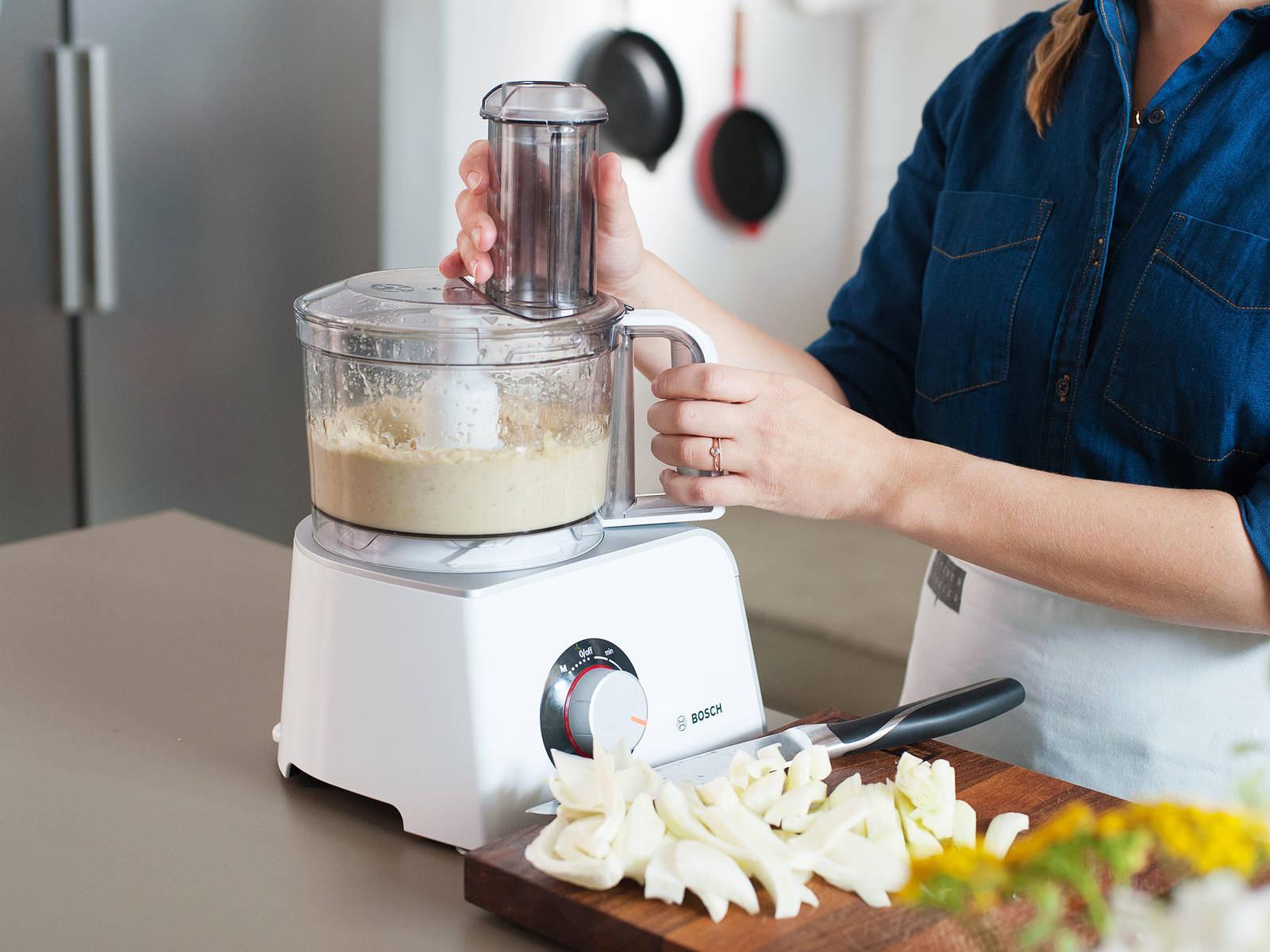 Weiße Bohnen, Knoblauch, einen Teil des Zitronensafts und Abriebs, sowie Parmesan in den Zerkleinerer geben. Mixen, bis sich eine einheitliche Masse formt. Olivenöl und Wasser hinzugeben und gut vermengen.