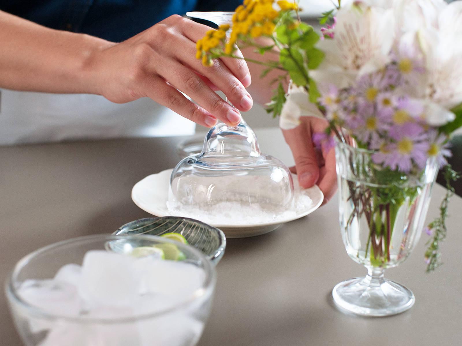 在盘子中放一些粗盐。沾湿2个玻璃杯的边缘,然后放到盘子中,裹上一圈粗盐,置于一旁。青柠切成楔形,用于装饰。