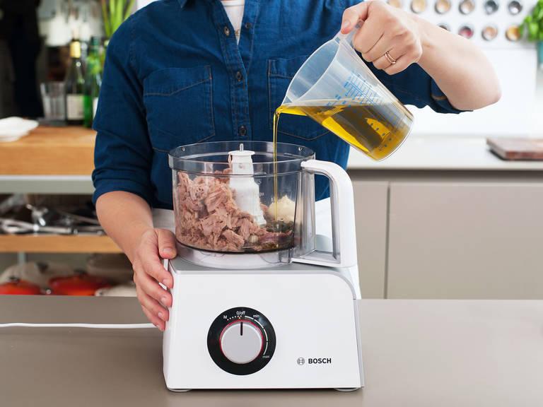 在此期间,制作酱汁。在一个搅拌机或者料理机中,搅打剩余的去皮蒜、凤尾鱼和酸豆,直至形成细末。放入蛋黄酱、橄榄油、半颗柠檬榨的汁和金枪鱼,搅打混合。撒盐与胡椒调味,如果喜欢可再加些凤尾鱼和酸豆。