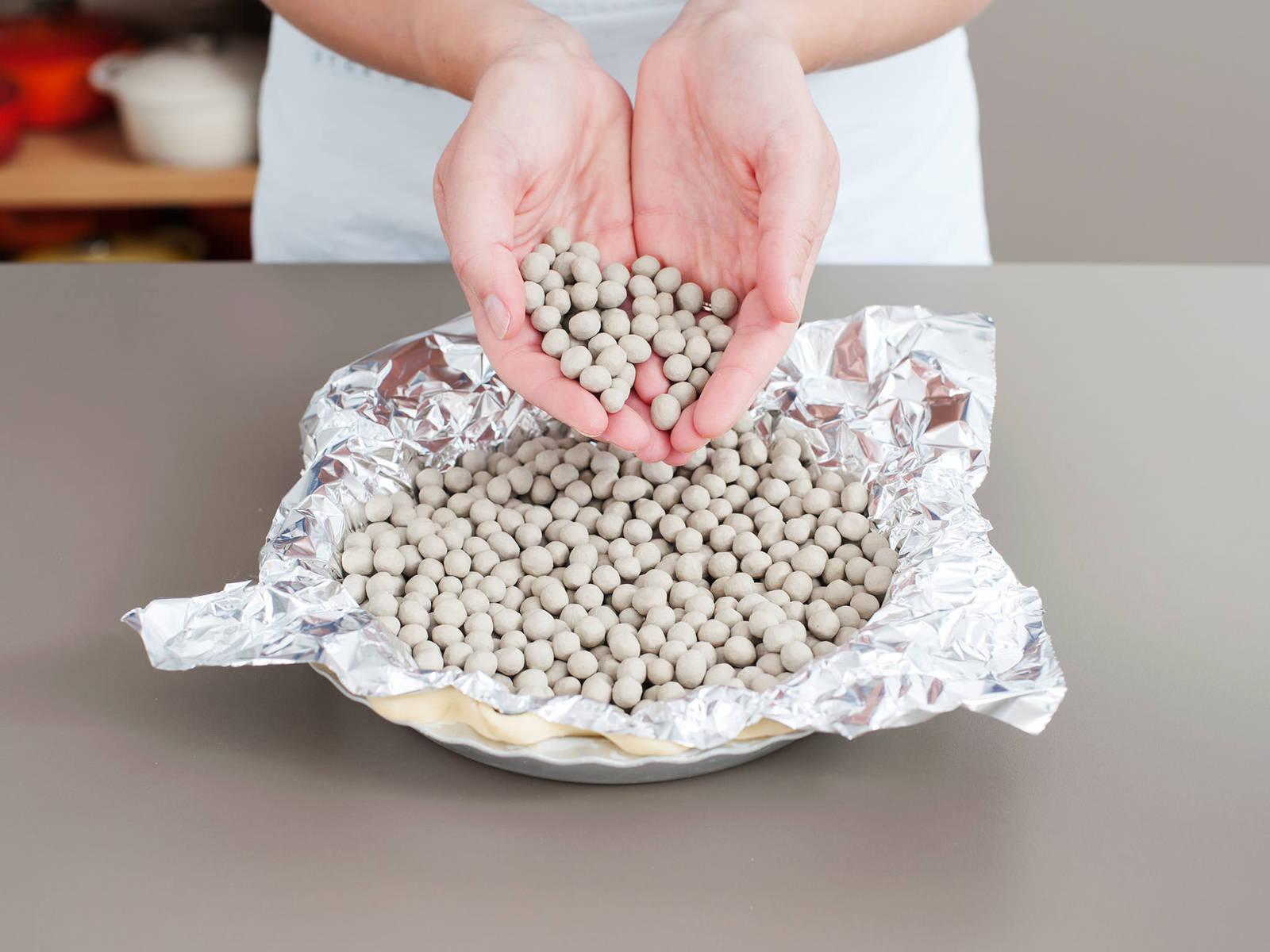 在撒好面粉的工作台上,将派皮擀成一个直径约30厘米的大圆。放到派盘中,剪去多余部分,并将边缘卷起,做出褶皱。将烤箱预热至200℃。用叉子在派皮上插孔,然后放到冰箱中冷藏15分钟。用铝箔盖住派皮,然后放进重石。烘烤20分钟,然后取出重石,然后继续烘烤至派皮开始变成金棕色,约需5分钟。静置放凉。