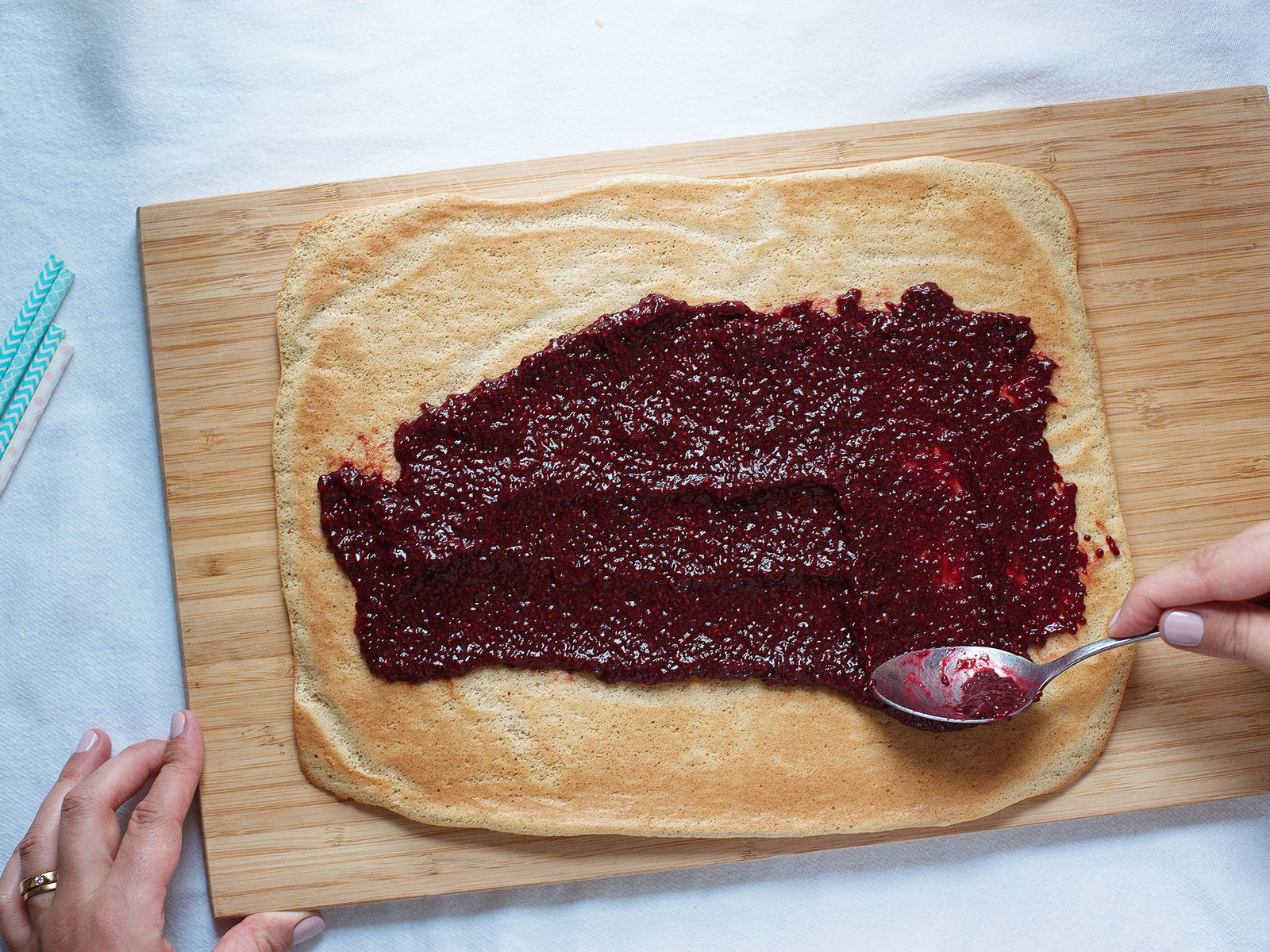 Take cake out of the oven and turn onto a clean kitchen towel. Remove parchment paper and, if necessary, turn cake so that the smooth side faces downwards. Coat cake with chia-raspberry jam. Use kitchen towel to roll up the cake tightly.