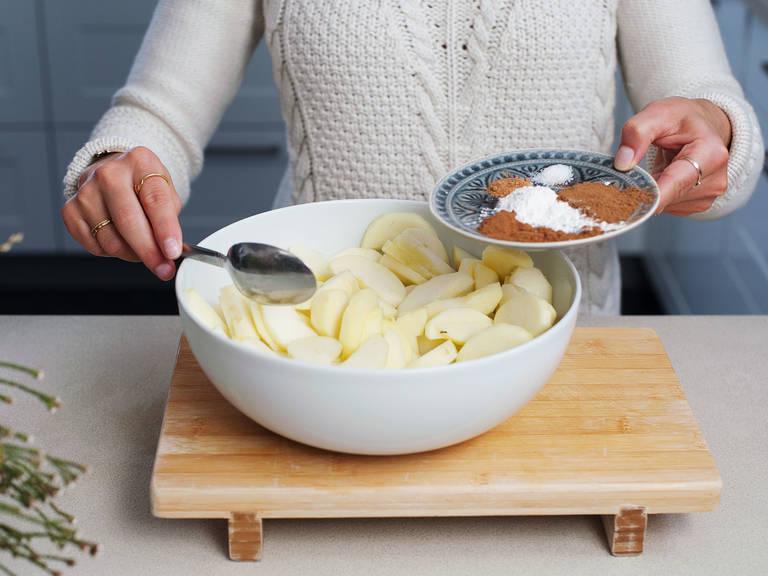 In einer großen Schüssel, Apfelscheiben mit etwas Zimt, Muskat, Zitronensaft, Agavendicksaft, Pfeilwurzelstärke, Kokosblütenzucker, Spekulatiusgewürz und einer Prise Salz vermengen.