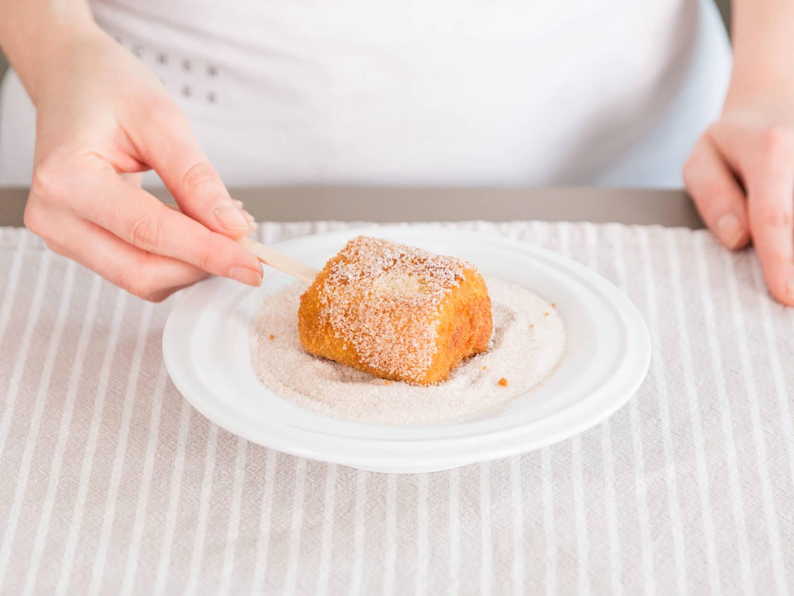 Die fertigen Leche Frita mit einem Eisstiel befestigen. Zimt mit Zucker in einem tiefen Teller oder einer flachen Schale mischen und die frittierten Quadrate darin wälzen, solange sie noch warm sind. Guten Appetit!