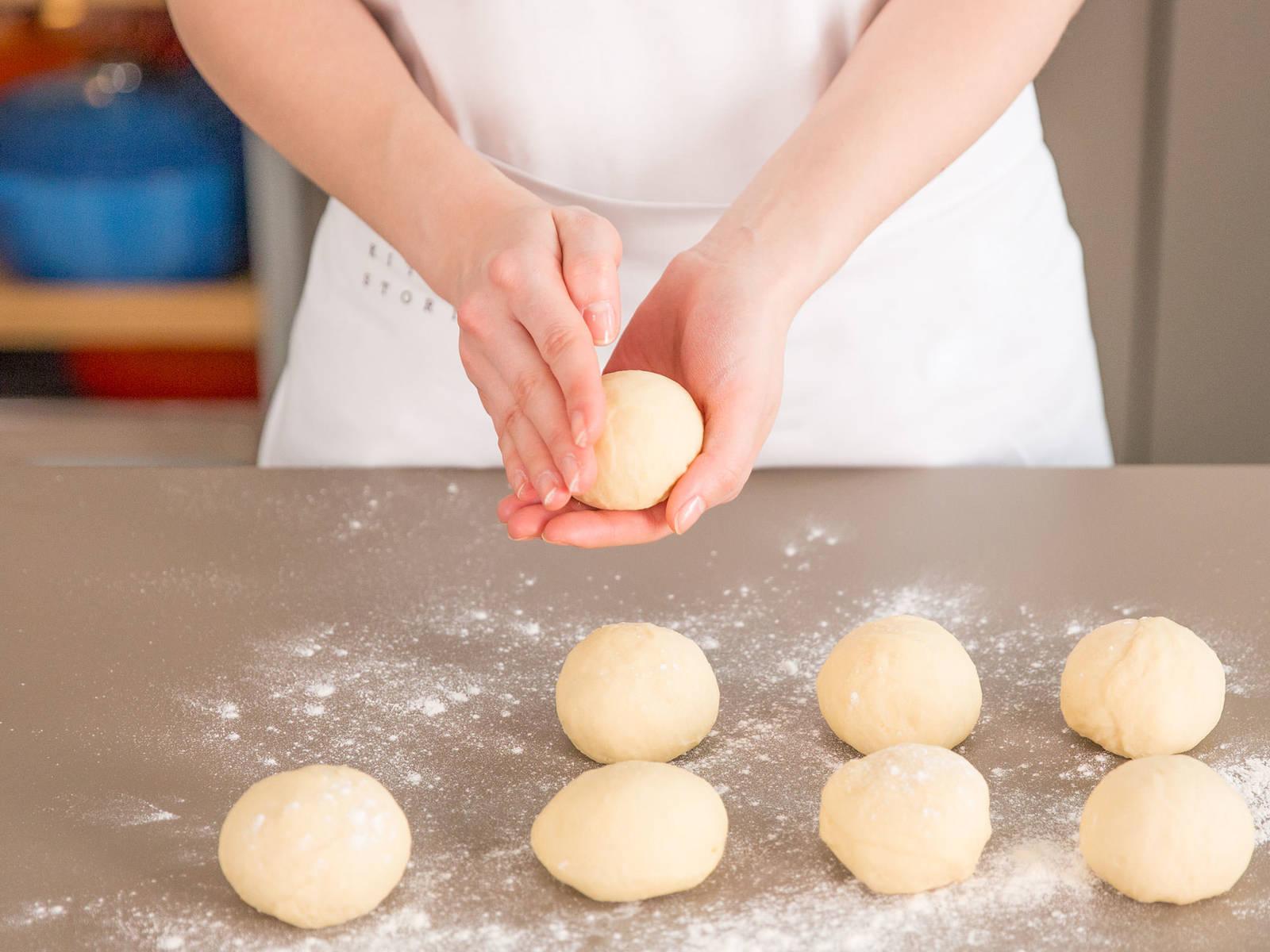 将发酵过的面团置于撒有面粉的工作台上,切半。将面团切成小拳头的大小。将小面团轻柔成球状。加盖,再发酵30分钟。
