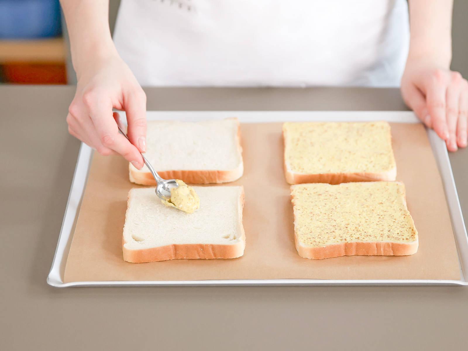 预热烤箱至200摄氏度。将一半吐司面包放在铺有烘焙纸的烤盘中,向面包上均匀涂抹一层芥末酱,然后放1片火腿、1片奶酪,再均匀涂抹一层摩尼沙司。