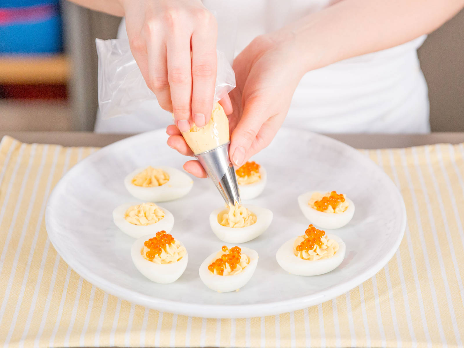 Transfer egg mixture to a piping bag and pipe into the halved egg whites. Top each egg with trout caviar and garnish with garden cress. Enjoy!