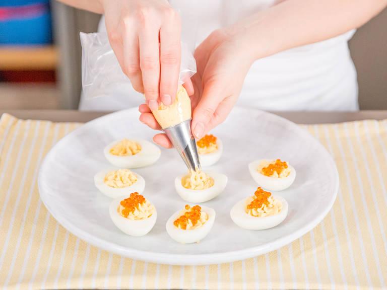 Die Eimischung in eine Spritztüte füllen und in die Eihälften spritzen. Jede Hälfte mit Forellenkaviar und Kresse bestreuen. Guten Appetit!