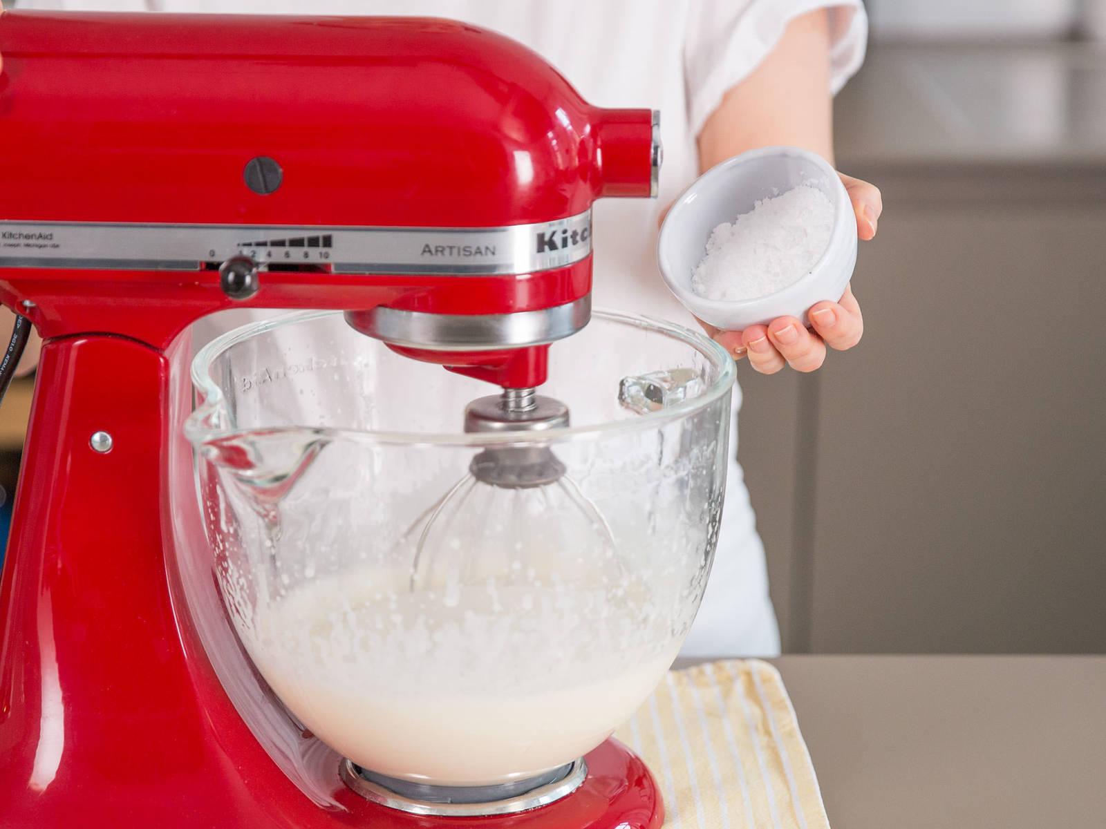 Erdbeeren in Scheiben schneiden. Sahne und Puderzucker in einer Küchenmaschine aufschlagen.