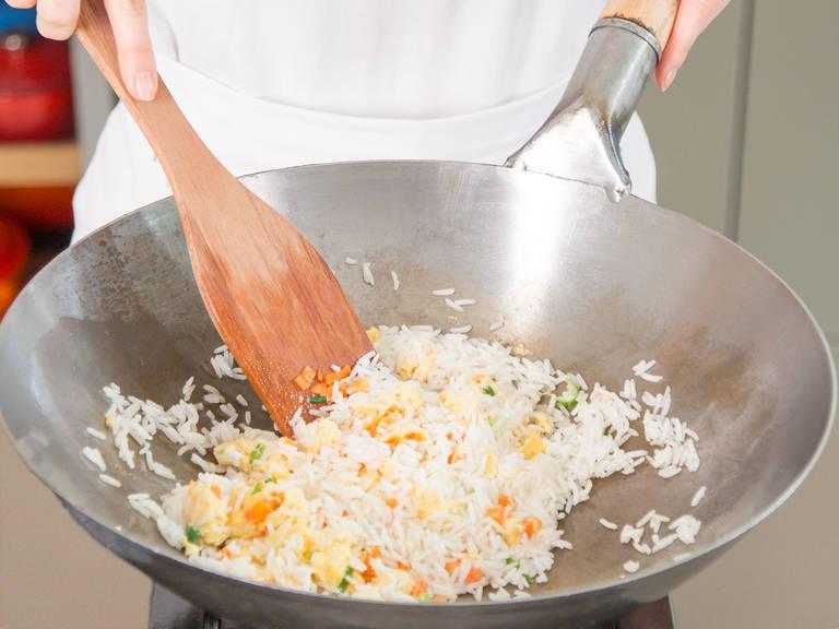倒入熟米饭和胡萝卜丁,放盐、胡椒和料酒调味,调大火翻炒。