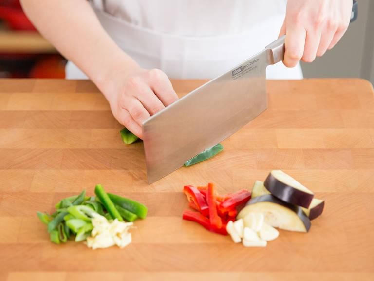 Aubergine in mundgerechte Stücke schneiden. Paprika in Streifen und Frühlingszwiebel in feine Ringe schneiden. Ingwer und Knoblauch in dünne Scheiben schneiden.