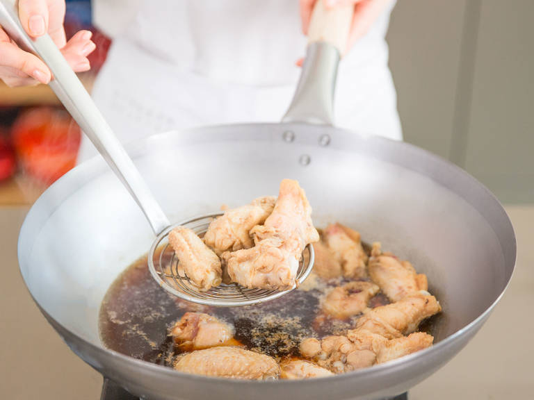 Fill wok a third of the way full with water and bring to a boil. Add chicken wings, blanch for approx. 3 – 5 min., and then remove from wok. Discard water.