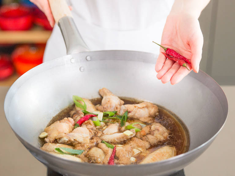 Cut green onion crosswise into slices. Add dried chilis, green onion, and ginger to wok. Bring to a boil on high heat and then reduce heat to low and simmer wings over low heat for approx. 15 min. until the sauce has thickened and wings are glazed.