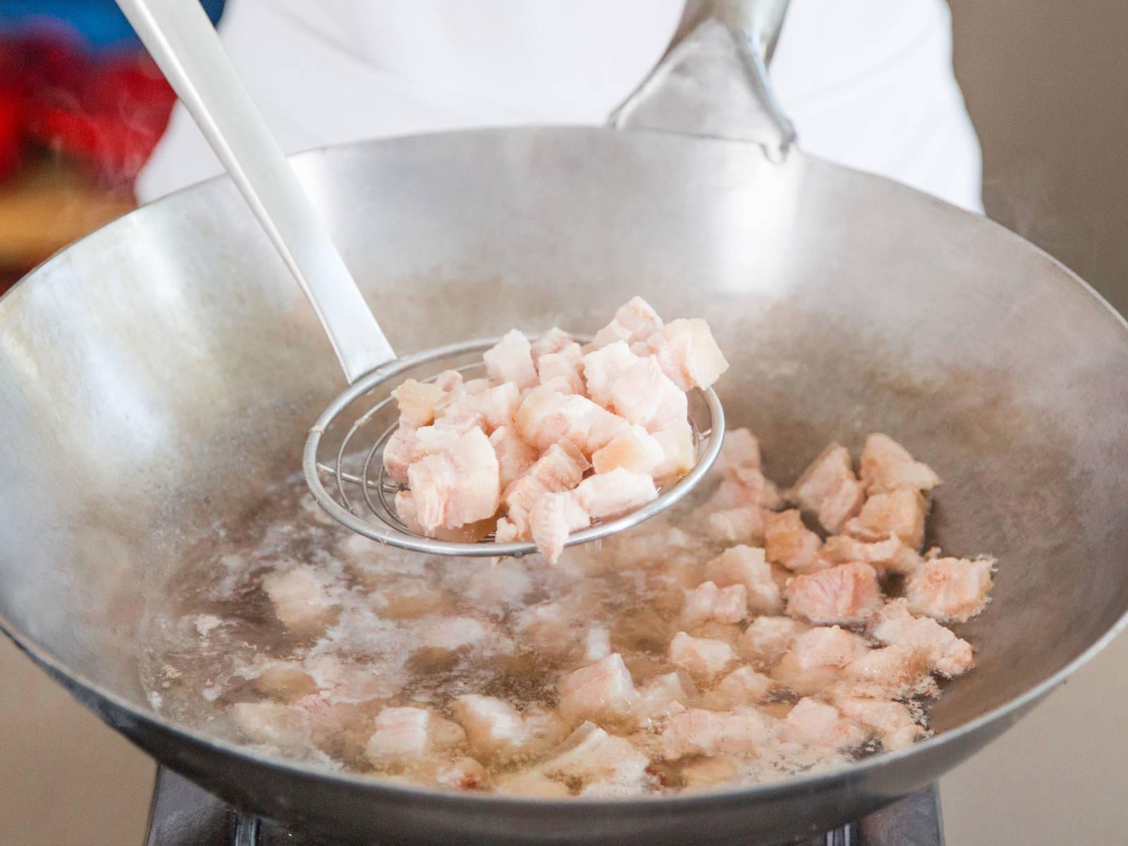 Wok zu einem Drittel mit heißem Wasser füllen. Schweinebauch hineingeben, aufkochen und ca. 5 - 7 Min. kochen. Wasser abgießen und Fleisch beiseitestellen.