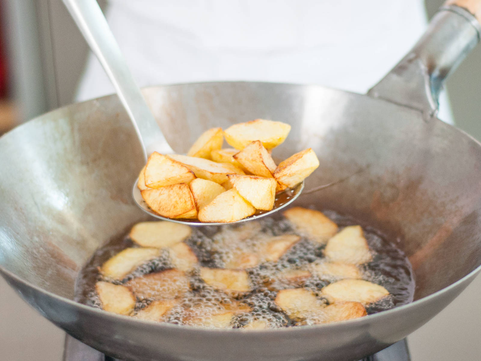Deep fry potatoes until golden brown, remove with a slotted spoon, and transfer to a paper towel-lined plate to drain.