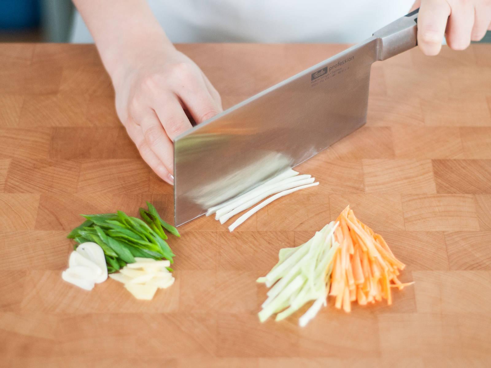 生姜和蒜去皮切片。胡萝卜削皮后切丝,香葱和卷心菜也切丝。