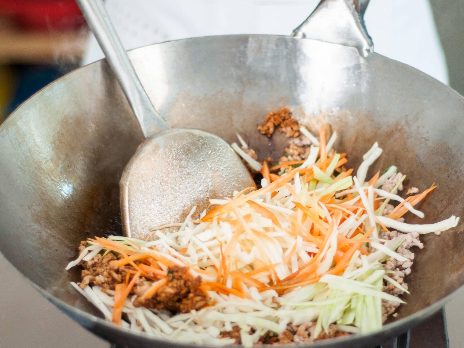 往炒锅中倒油,翻炒猪肉末2-3分钟,直至猪肉变棕色。加入胡萝卜和卷心菜,小火翻炒至蔬菜变软,约需6-7分钟。放入生姜片、蒜片和香葱末。用五香粉、盐、胡椒和老抽调味。