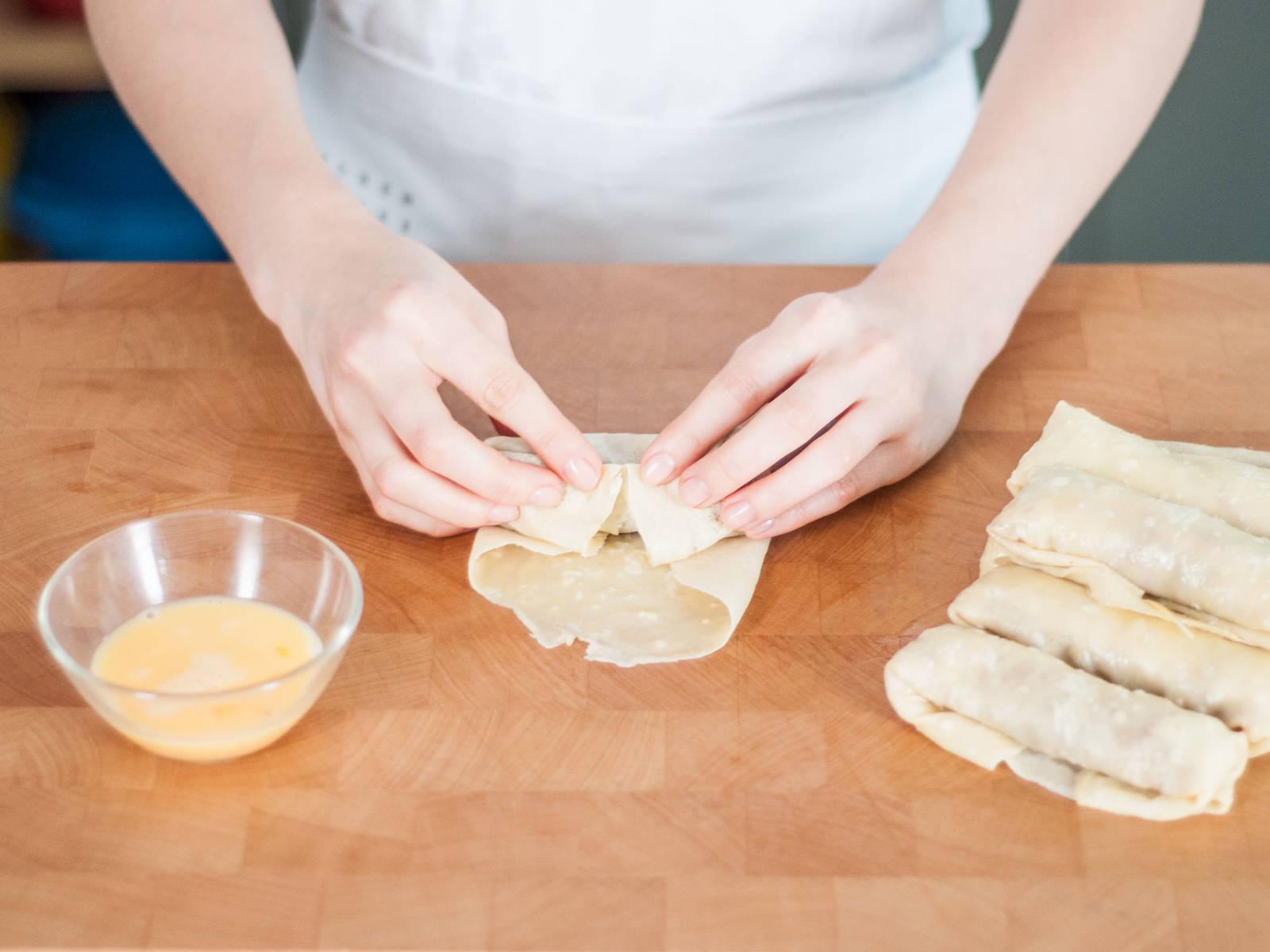 将鸡蛋、面粉和水放到小碗中,搅拌混合。将猪肉馅放入春卷皮中,卷上,封住边缘。涂抹上面糊。