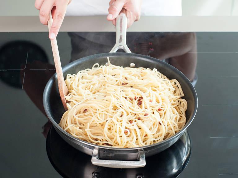 Pasta in die Pfanne geben und schwenken, bis sie vom geschmolzenen Fett bedeckt sind.