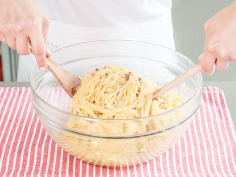 Die Pasta zusammen mit der Hälfte des beiseite gestellten Kochwassers in die Servierschüssel zu der Eimischung geben und alles schnell und gleichmäßig miteinander vermischen, bevor die Eier zu Rührei werden. Vermengen, bis die Mischung cremig wird, nach Bedarf mehr Kochwasser hinzufügen.