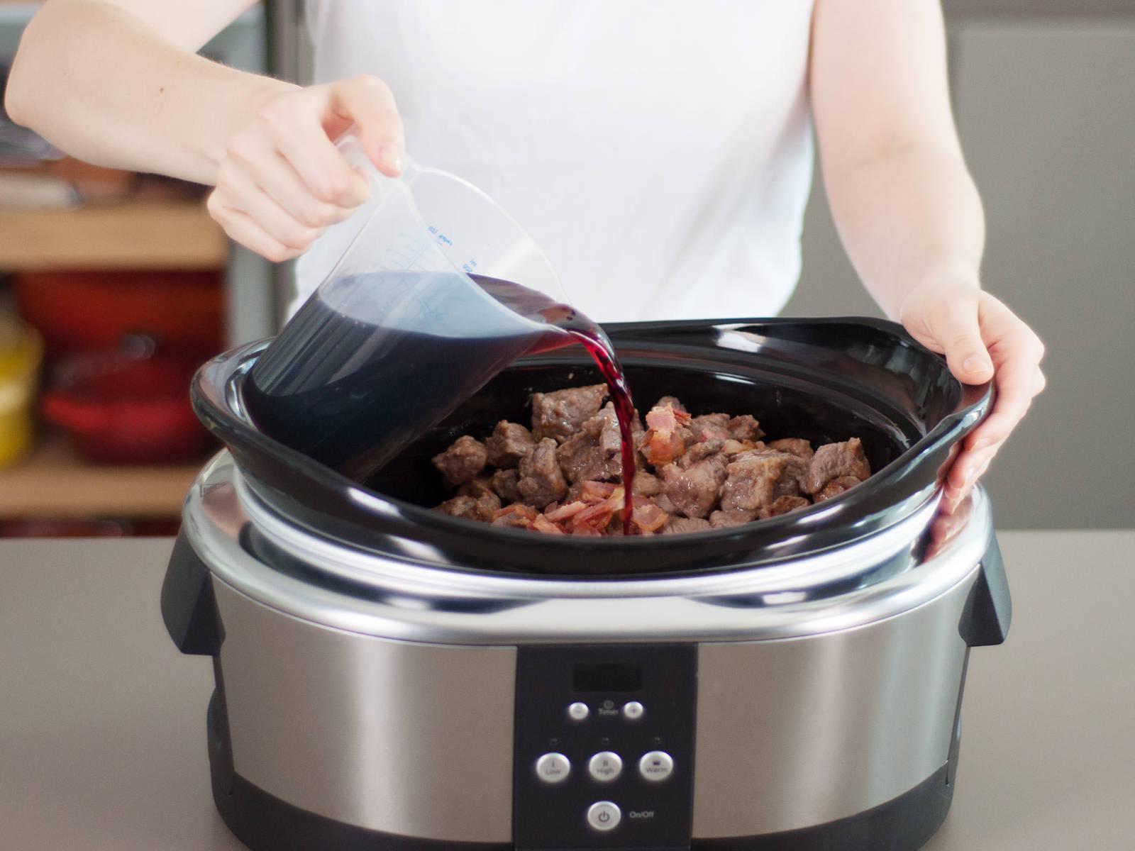 之后, 将高汤,番茄酱,百里香,月桂叶和红酒一起加入炖锅。加盖,慢火炖6-8小时