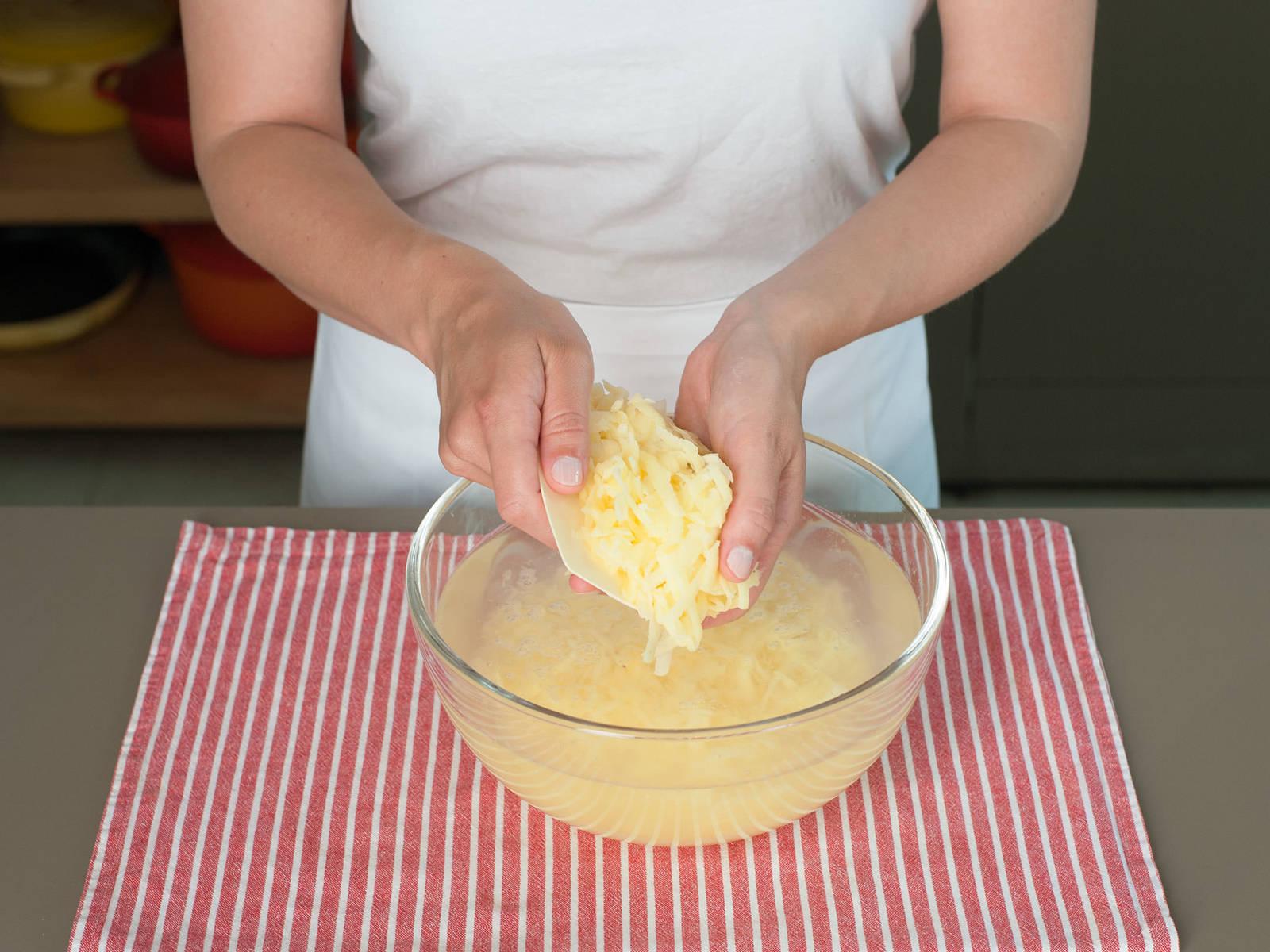 Eine große Schüssel mit kaltem Wasser füllen und die Kartoffelraspeln dazugeben. Sobald das Wasser komplett milchig ist, Wasser abgießen und die Kartoffelraspeln unter kaltem Wasser abspülen. Anschließend in ein Küchenhandtuch geben und über der Spüle so viel Wasser wie möglich auswringen. Kartoffelraspeln zurück in die Schüssel geben, kurz auflockern, und erneut im Küchenhandtuch auswringen.