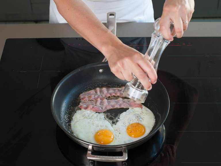 Fry bacon in the same skillet set over medium-high heat until crispy. Add butter to skillet and fry eggs in butter until whites are set and edges are crispy. Divide bacon, eggs, and hash browns evenly among serving plates and garnish with chives, salt, and pepper. Enjoy!