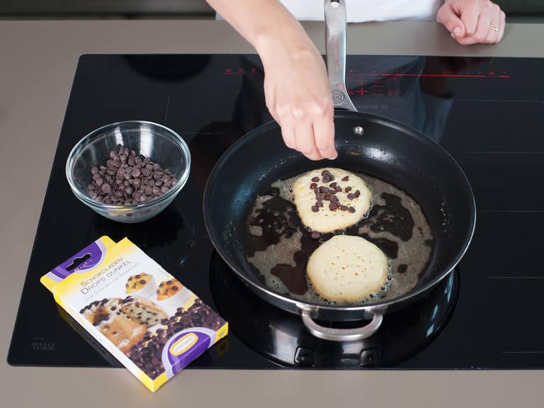 Etwas Butter bei mittlerer Hitze in der Pfanne schmelzen. Teig portionsweise in die Pfanne geben und falls gewünscht Schokodrops darüber streuen. Wenn sich auf der Oberfläche Bläschen bilden, umdrehen und für weitere ca. 1 - 2 Min. goldbraun ausbacken. Mehr Butter verwenden, um das Ankleben oder Verbrennen zu verhindern. Auf einen Teller geben und mit Butterflocken und Ahornsirup genießen.