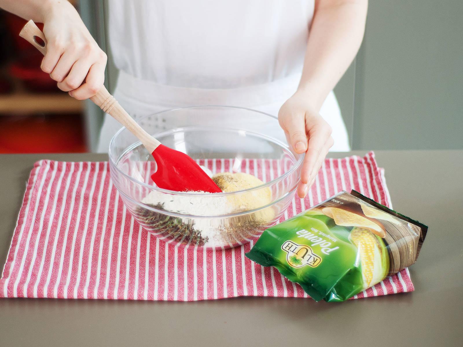 将烤箱预热至200℃。在一个大碗中混合粗玉米面、面粉、盐、胡椒、草本末和泡打粉。