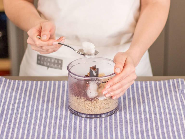 Einen Teil der gerösteten Kokosflocken, Kakaopulver, Kokosöl, Stevia und eine Prise Salz in den Zerkleinerer geben und gut vermengen bis eine einheitliche Masse entsteht. In eine große Schüssel geben und ca. 1 Stunde in den Kühlschrank stellen bis die Masse fest ist.
