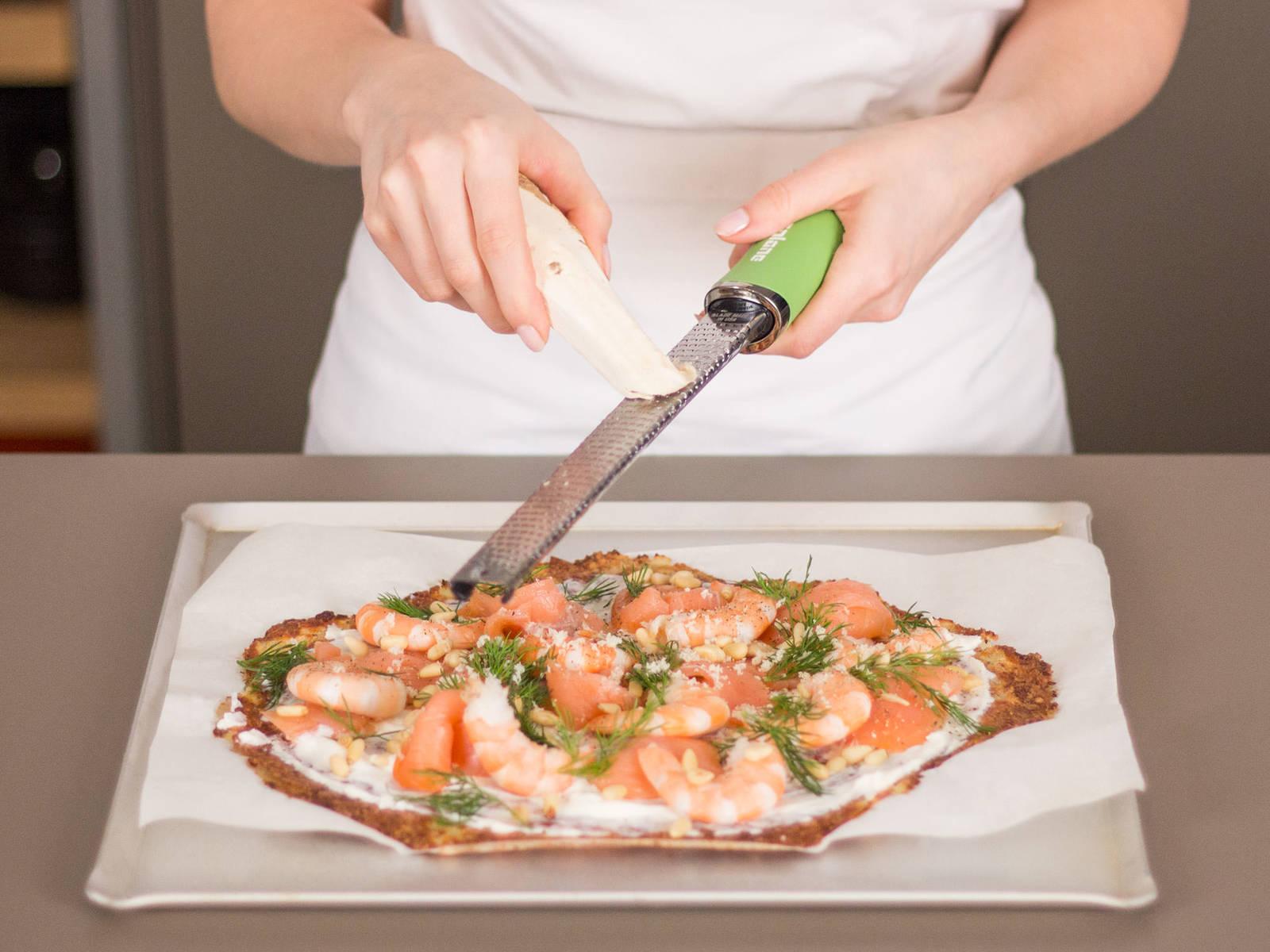 Ricotta gleichmäßig über den Teig geben. Anschließend mit Lachs, Shrimps, Pinienkernen und frisch geriebenem Meerrettich belegen. Mit frischem Dill garniert servieren. Guten Appetit!