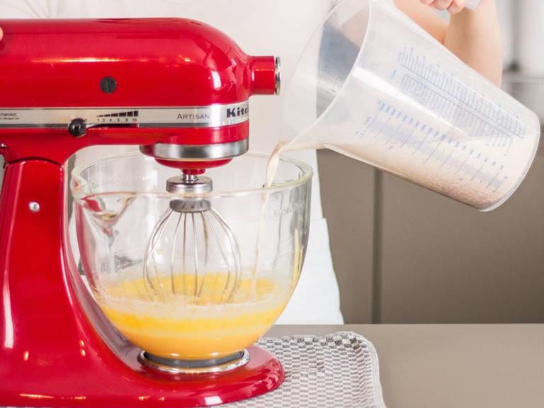 Auf niedriger Stufe die aufgekochte Mandelmilchmischung langsam zu den Eigelben gießen. Gut verrühren.