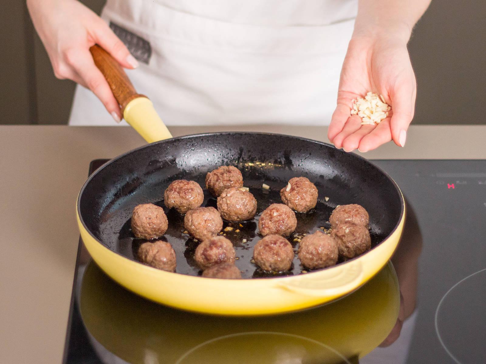 用盐与胡椒粉为牛肉末调味,然后将牛肉末揉成乒乓球大小的肉丸。在大煎锅中用中温加热适量植物油,放入肉丸煎4-6分钟,至肉丸呈棕色。待肉丸即将熟透时放入蒜碎。