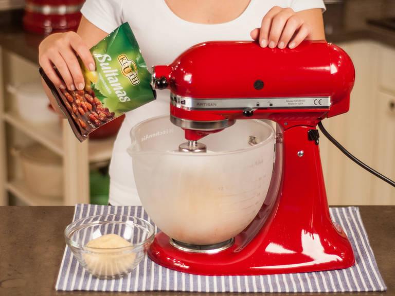 将烤箱预热至180摄氏度。取出约1/4面团备用。将剩余的面团和杏仁片、糖渍橙皮和柠檬皮、葡萄干混合,继续揉至完全均匀。