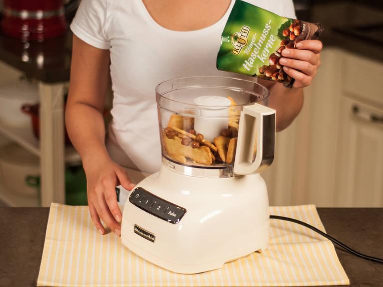 将烤箱预热至180摄氏度。将杏仁饼、榛子和融化的黄油放入食品加工机中搅拌至顺滑。
